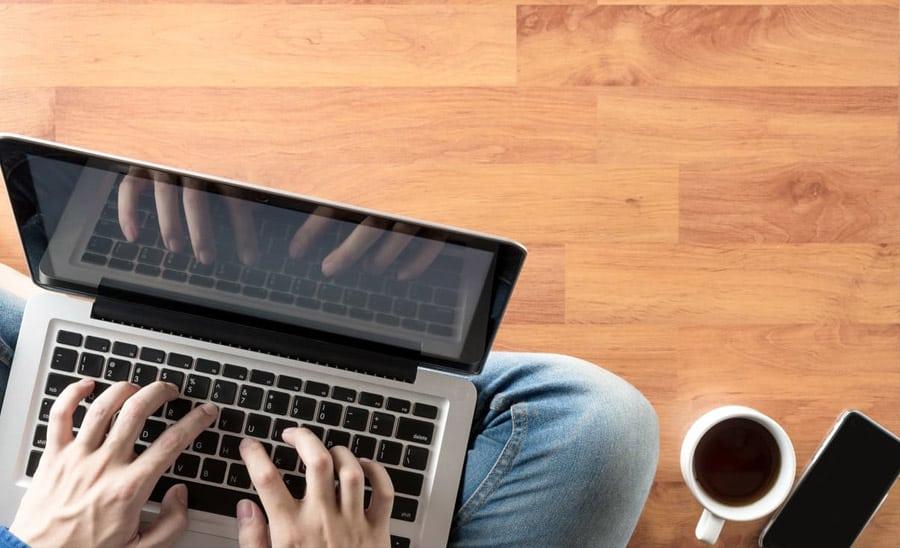 איש מקליד במחשב נייד לגבי סליקת אשראי לאומי מקס עסקים