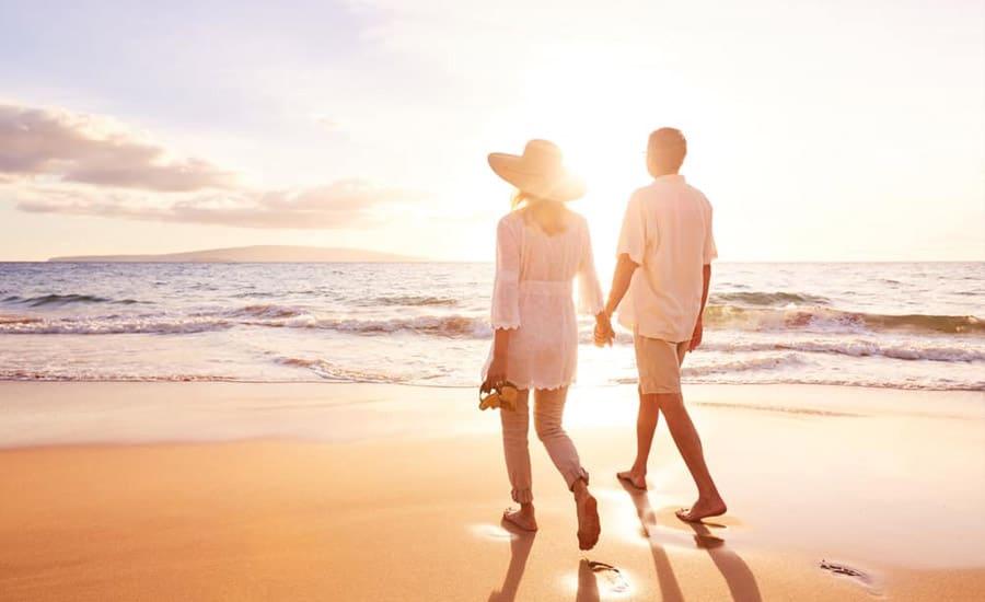 זוג הולך יד ביד בחוף בקיסריה