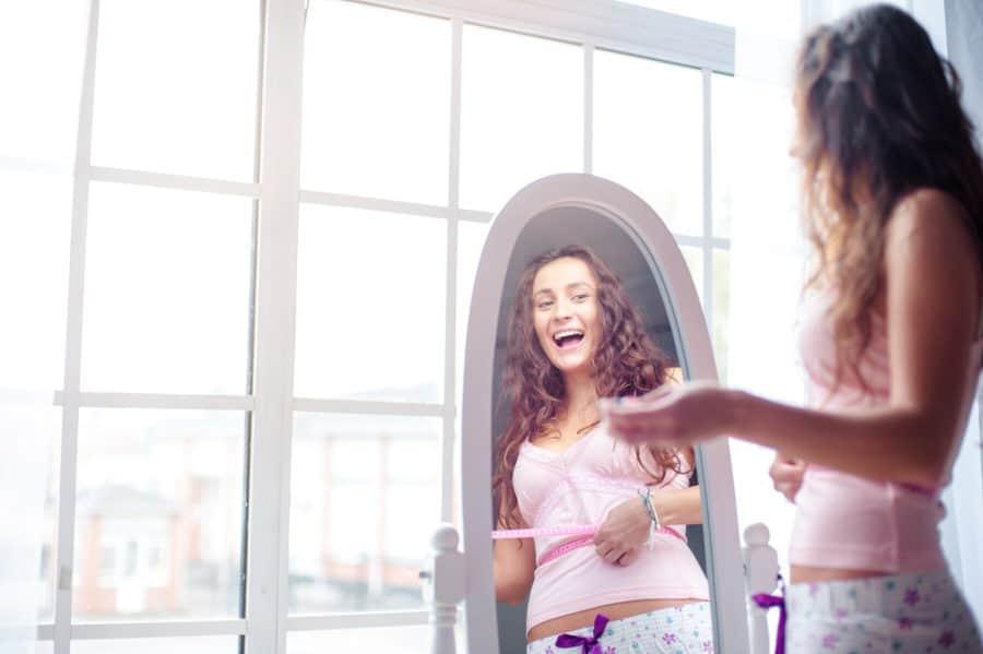 אישה מסתכלת במראה ושמחה מהירידה במשקל