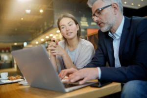 אישה צעירה מתבוננת במחשב לאחר הסבר מאיש ביטוח
