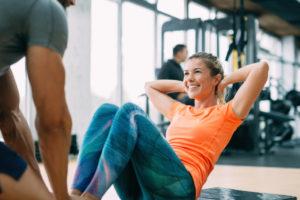 אימון כושר בחדר כושר שבו האישה מבצעת כפיפות בטן